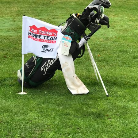 Golf bag next to Home Team flag in ground